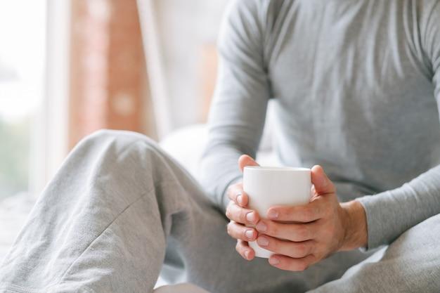 Любимый напиток комфорта. утро нового дня. человек сидит, держа чашку горячего напитка.