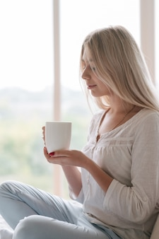 Любимый напиток комфорта. каждый утренний ритуал. женщина, держащая чашку горячего напитка.