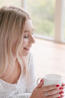 好きなコンフォートドリンク。健康的な朝の習慣。熱い飲み物のカップを保持している女性。