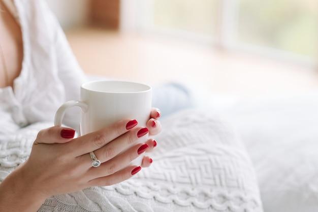 Любимый напиток комфорта. утренний ритуал. руки женщины с чашкой горячего напитка.
