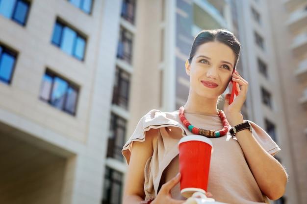 好きな飲み物。一杯のコーヒーを押しながら笑って喜んでうれしそうな女性