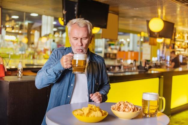 Любимый напиток. хороший приятный мужчина держит стакан с пивом, находясь в спортивном клубе