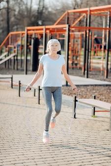 好きな運動。野外で運動しながらロープをジャンプする細い女性に警告