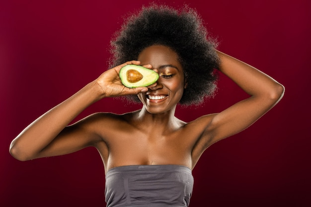 Любимый фрукт. довольно веселая женщина улыбается, наслаждаясь едой авокадо