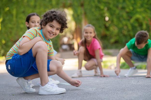 Любимое занятие. кудрявый улыбающийся мальчик в футболке и шортах рисует с друзьями мелками в парке в летний день