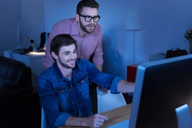 좋아하는 직업. 쾌활한 기뻐하는 남성 프로그래머가 동료에게 뭔가를 보여주는 동안 미소하고 화면을 가리키는