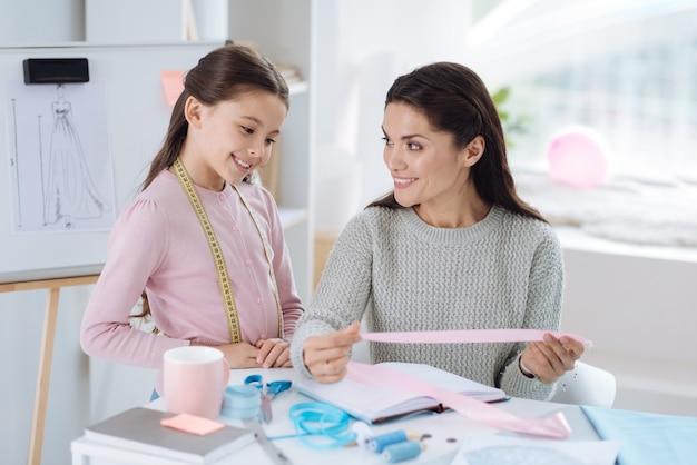 Любимая работа. радостная и позитивная умная женщина, держащая розовую ленту и смотрящая на свою дочь при разработке одежды