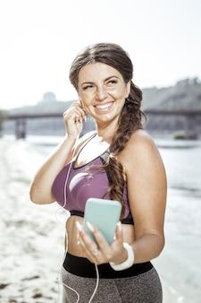 好きな音楽。橋の上に立っている間彼女の好きな歌を聞いてポジティブな幸せな女性
