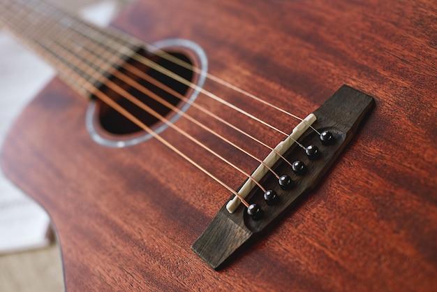 Любимый музыкальный инструмент крупным планом на красивой коричневой гитаре с шестью металлическими струнами музыки