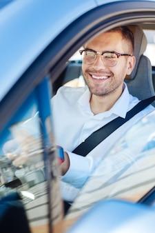 好きな職業。彼の車で運転を楽しみながら笑顔で喜んで幸せな男