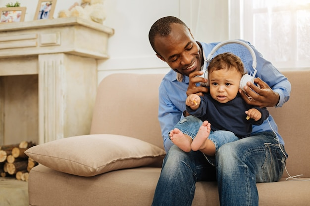 Favourite singer. attractive smiling inspired afro-american man holding his cute little with headphones on his head and listening to music while sitting on the couch