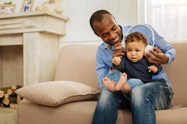 好きな歌手。魅力的な笑顔に触発されたアフリカ系アメリカ人の男性は、頭にヘッドフォンを付けてかわいい子供を抱き、ソファに座って音楽を聴いています