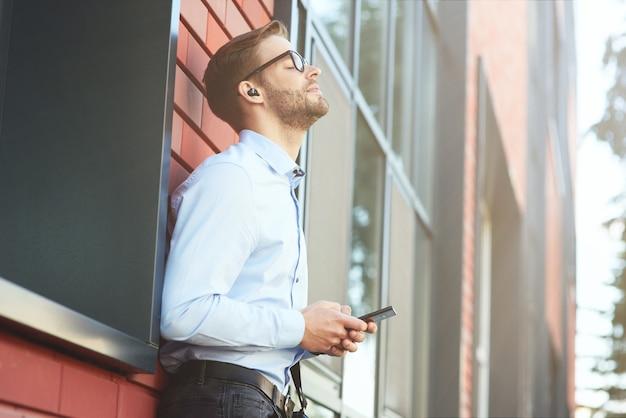 무선 이어폰으로 음악을 듣는 젊은 행복한 사업가의 가장 좋아하는 노래 측면