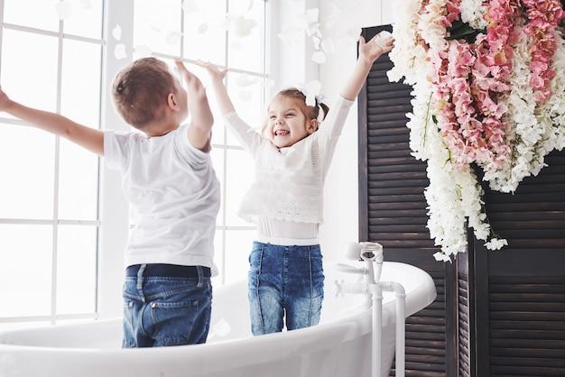 Ребенок играя с лепестками розы в домашней ванной комнате. маленькая девочка и мальчик fawing веселья и радости вместе. детство и воплощение мечты, фантазии, воображения