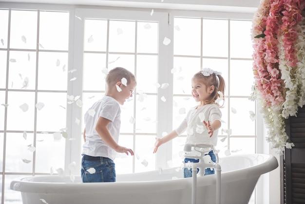 Ребенок играет с лепестками косули в домашней ванной комнате. маленькая девочка и мальчик fawing веселья и радости вместе. детство и воплощение мечты, фантазии, воображения