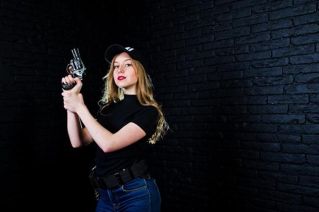 Fbi female agent in cap and with gun against dark brick wall.