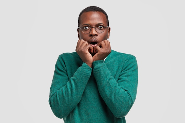 Fearful black businessman keeps both hands near mouth, looks with shock , dressed in casual jumper, stands against white space