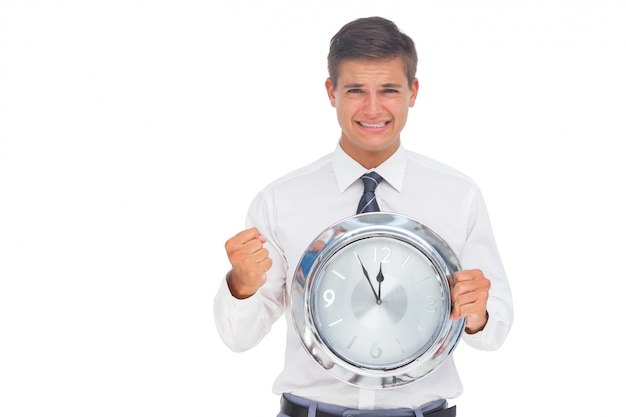 Fearful businessman holding and looking at clock