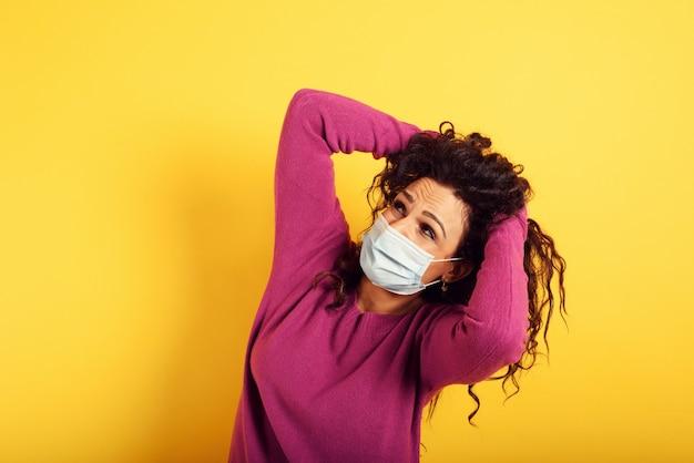 Испуганное выражение лица женщины, которая боится заразиться коронавирусом на желтом.