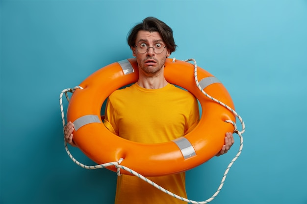 Fearful man afraids of swimming in deep sea, poses with inflated lifebuoy, listens advice of instructor, wears spectacles and glasses, poses