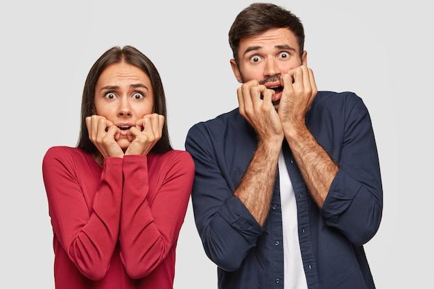 두려운 기절 감정적 인 젊은 여성과 남자는 긴장하게 손가락을 물고 겁에 질린 표정으로 응시하며 불안을 느낍니다.