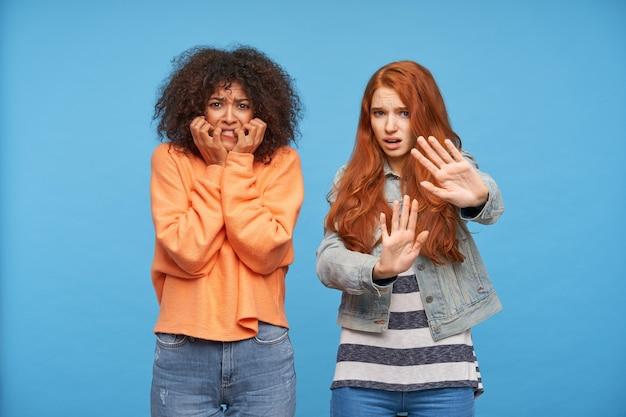カジュアルな服を着た恐ろしい若い魅力的な女性は、怖い顔をして眉を眉をひそめ、青い壁にポーズをとって手を上げます