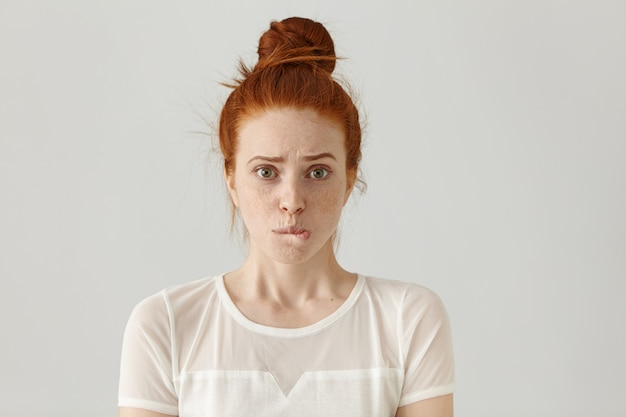 Fearful young caucasian female with ginger hair dressed in white blouse having confused guilty look, biting her lower lip, feeling sorry for doing something wrong and making terrible mistake