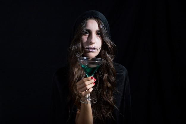 Giovane donna spaventosa con il bicchiere di vino