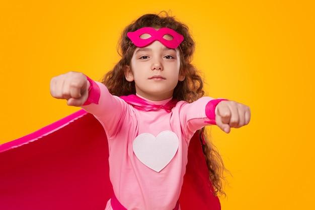 カメラに向かって飛んでいる大胆不敵なかわいいスーパーヒーローの女の子