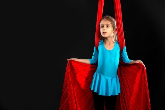 Бесстрашная симпатичная маленькая девочка в синем гимнастическом костюме показывает красную ленту на черном фоне.
