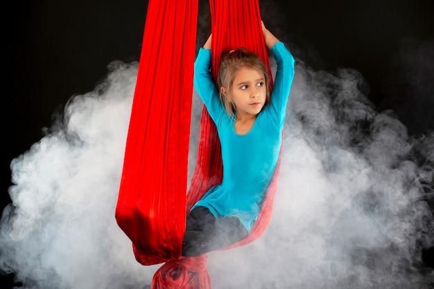 Бесстрашная симпатичная маленькая девочка в синем гимнастическом костюме показывает красную ленту в воздушном трюке, окруженную дымом на черном