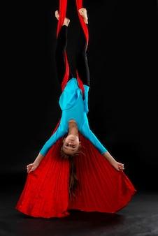 파란색 체조 정장에 두려움없는 예쁜 소녀는 스턴트 공중 빨간 리본을 보여줍니다