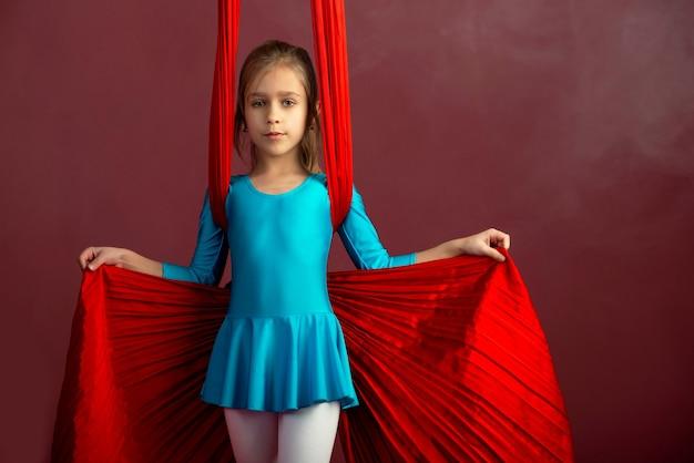 青い体操のスーツを着た大胆不敵なかわいい女の子は、スタント空中赤いリボンを示しています