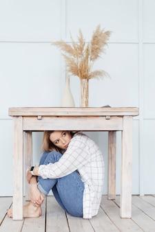 Опасения. женщина спряталась под столом от своих страхов.