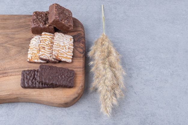 大理石の上のクッキーとウエハースとボードの横にある羽草の茎