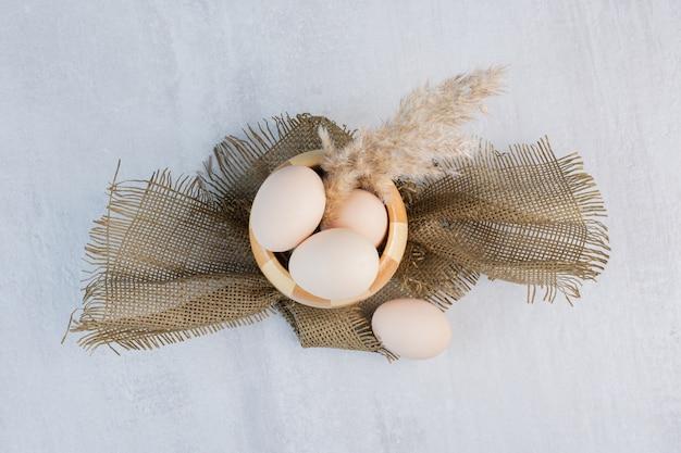 大理石のテーブルの市松模様のボウルに羽草の茎と卵。