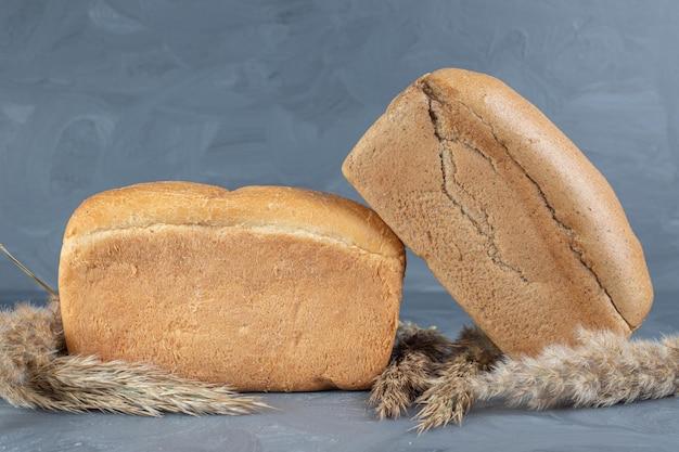 Gambi di erba piuma e pagnotte di pane si raggruppano sul tavolo di marmo.