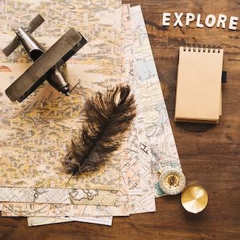 Feather and plane near compass and notebook