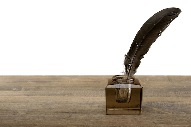 Перо гусиное перо и стеклянная чернильница, изолированные на белом фоне