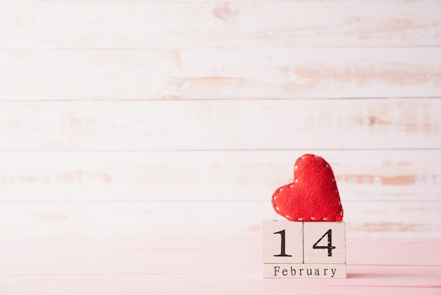 February 14 text on wooden block with red heart on wooden background.