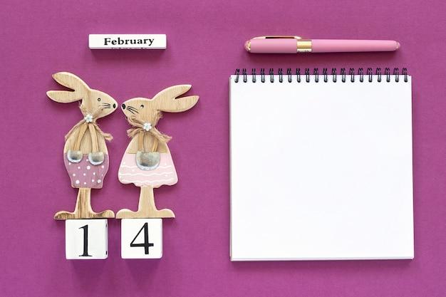 14 февраля пара кроликов, блокнот с ручкой на фиолетовом фоне