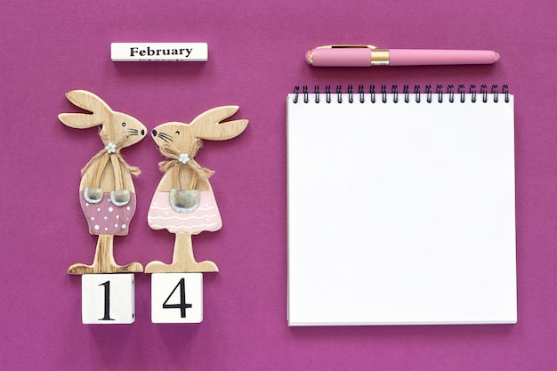 February 14th pair of rabbits, notebook with pen on purple background