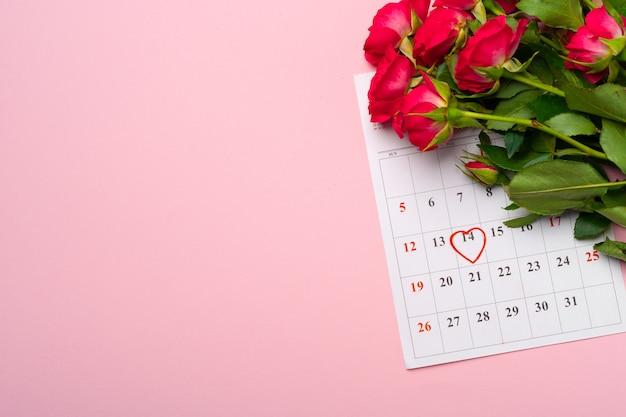 2月のカレンダーと赤いバラの上面図