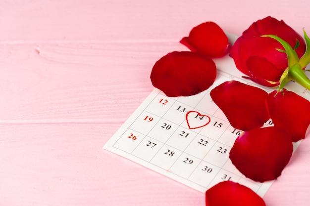 Страница календаря февраля с красной розой на розовом деревянном столе крупным планом