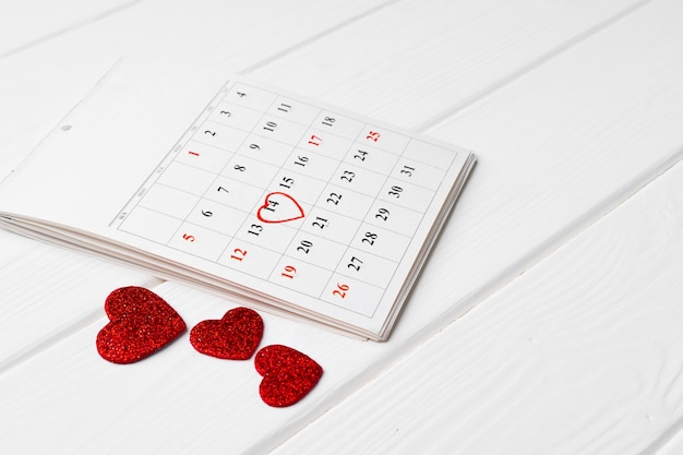 February calendar and three red hearts on wooden close up