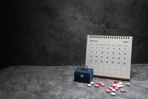 小さな青いギフトボックスと色とりどりのハート型チョコレートが付いた2月のカレンダー