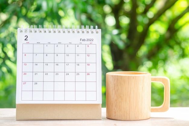 2월 달, 주최자를 위한 캘린더 데스크 2022는 녹색 자연 배경을 가진 나무 테이블에 대한 계획 및 알림을 제공합니다.