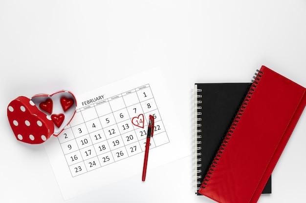 キャンディーのハートの形と白い背景の上のノートブックと14日のカレンダーテンプレートの2月