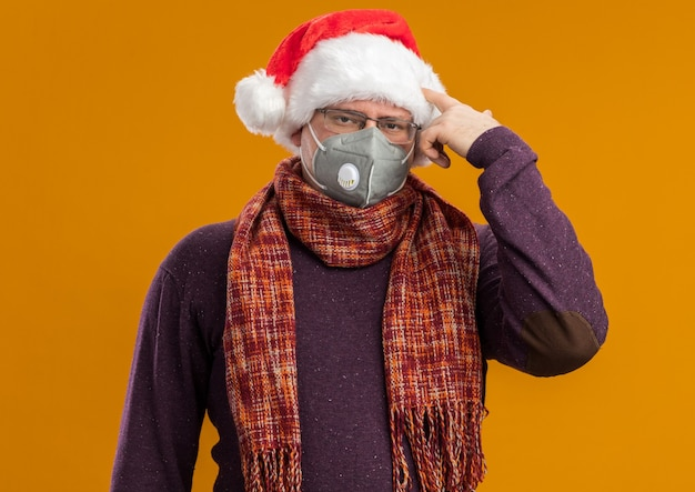 Сытый по горло взрослый мужчина в очках с защитной маской и шляпе санта-клауса с шарфом на шее смотрит в камеру, делая жест самоубийства, изолированный на оранжевом фоне