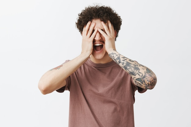 Fed up depressed and stressed guy in despair with curly hair and tattooed arm covering face with palms from painful feeling inside soul yelling or screaming loosing temper over gray wall